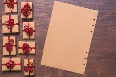 Prezenty zawijający w faborku i łęku Kraft czerwieni i papieru, papier na drewnianym tle Zdjęcia Royalty Free