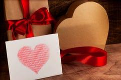 Prezenty zawijający z czerwonym faborku i kartonu sercem Zdjęcie Royalty Free
