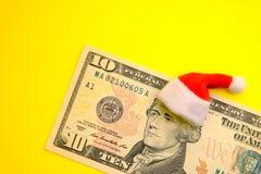 Prezydent Hamilton w czerwonym Święty Mikołaj kapeluszu na dziesięć dolara amerykańskiego rachunku przeciw jaskrawemu żółtemu tłu zdjęcia royalty free