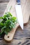 Prezzemolo organico fresco con il coltello sul tagliere di legno Immagini Stock Libere da Diritti