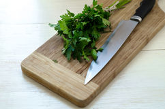 Prezzemolo organico fresco con il coltello sul tagliere di legno Immagine Stock