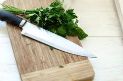 Prezzemolo organico fresco con il coltello sul tagliere di legno Immagine Stock Libera da Diritti