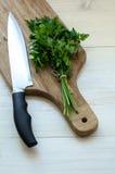 Prezzemolo organico fresco con il coltello sul tagliere di legno Fotografie Stock Libere da Diritti