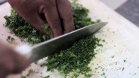 Prezzemolo organico fresco con il coltello sul tagliere di legno DOF basso video d archivio