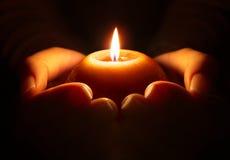 Prière - bougie dans des mains Photo stock