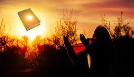 Prière de femme pieuse avec le lever de soleil Image stock