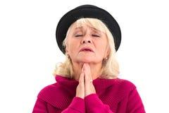 Prière de vieille dame d'isolement Photographie stock