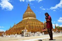Prière thaïlandaise de femme de la pagoda de Shwezigon ou du Shwezigon Paya dans Bagan, Myanmar photo libre de droits