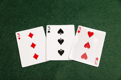 A Prial Of Threes. Three threes laid out on a green baize background Royalty Free Stock Image