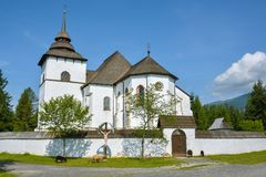 Sheeps grazing in front of old church in open air museum in Pribylina. Pribylina, Slovakia - August 10, 2014: Sheeps grazing in front of old church in open air stock image