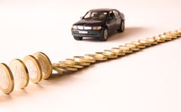 Price of black car falls. Queue of euro coins falls, red german car Stock Image