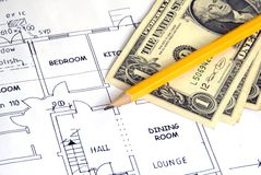 The Price of Building. Dollar bills on building plans, and pencil, high angle Royalty Free Stock Photo