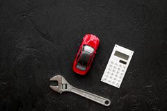 Price of car repair. Wrench near car toys and calculator on black background top view copyspace Stock Photo