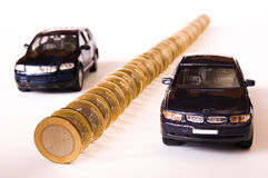 Price of cars. Queue of euro coins and two cars, conceptual image Stock Photography