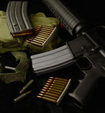 The Price of Freedom is Everlasting Vigilance. AR-15 on Black with Clips of Ammunition Royalty Free Stock Photo