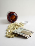 The price of health care. A pile of spilled tablets with Money Stock Photography