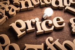 Price Idea Topic. Price word in scattered wood letters with glowing white light bulb royalty free stock image