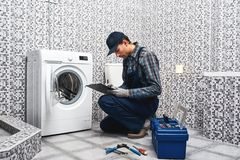 Price of plumbers work. Working man plumber writing price list. Near a washing machine in laundry stock photo