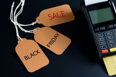 Price tag and credit card machine on black table background, Black Friday concept. Royalty Free Stock Photography