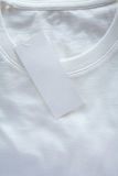 Price tag hang over white t-shirt Stock Images