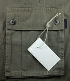 Price tag over textured pocket. White empty price tag over textured pocket Stock Image
