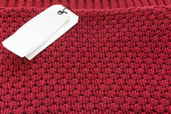 Price tag sale label on red knitted wool fabric texture backgrou Stock Photography