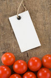 Price tag and tomato vegetable at wood background Royalty Free Stock Photo