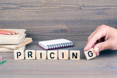 Pricing. Wooden letters on dark background