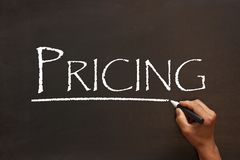 Pricing Word Concept. Pricing word handwriting with white chalk marker on a blackboard. Business concept stock photo