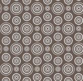Prickar cirklar den vita sömlösa modellen på mörk brunt Fotografering för Bildbyråer