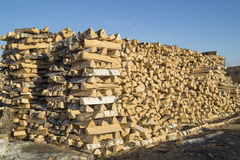 Pricked firewood built in stack of logs on background blue sky. Pricked firewood from birch for stove built in stack of logs on background blue sky Stock Photos