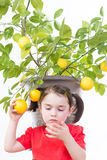 Prickly Lemon Thorns. Young girl inspects hand after getting punctured by a prickly lemon thorn stock photo