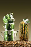 Prickly tea-party. A studio view of a tea pot and two cups in a fancy tea set along with a green cactus on a gravel surface Royalty Free Stock Images
