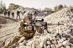 Prickskytten täcker den offensiva truppen av soldater Fotografering för Bildbyråer