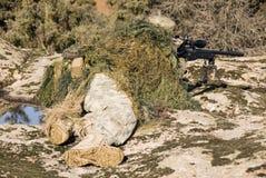 Prickskyttghillie klädde att peka med prickskyttgeväret L96-A1 - 1 Royaltyfri Fotografi