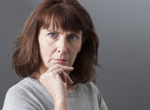 Pride and arrogance for displeased mature woman. Pride and arrogance - displeased mature woman complaining, expressing her disagreement and irritation,gray royalty free stock image