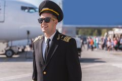Hilarious airman near big plane. Pride of aviation. Joyous pilot is standing outside and looking ahead with smile. He wearing sunglasses. Waist up portrait Royalty Free Stock Photo