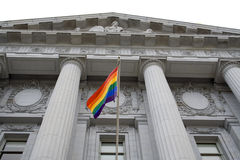 Pride flag at city hall. Lesbian, gay, bisexual, and transgender pride flag flying outside a government building stock image