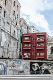 Pride of Ownership shown with well maintained building beside old architecture. Well maintained red building among derelict buildings with graffiti and murals stock images