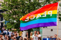 Pride parade in action. Famous rainbow peace flag above the crowd of demonstrators. Event celebrating lesbian, gay, bisexual,. Vilnius, Lithuania - July 27, 2013 stock photo