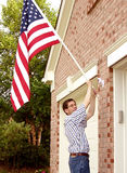 Pride and Patriotism (1). Raising The American Flag A man attaches the American flag into the bracket on the exterior of a brick house on the 4th of July stock photo