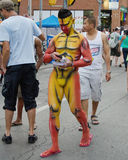 Pride Week Body Painted Man. TORONTO, CANADA- JUNE 30, 2013: Man with the body painted and used as walking advertisement during Pride Week in downtown Toronto Royalty Free Stock Photos