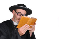 Priest with bible. Middle aged devout priest in with bad eye sight.  Religious male person reading the bible with glasses Stock Image