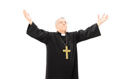 Priest in black mantle gesturing with hands Stock Images