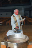 A priest blesses the oils during a child`s baptism Stock Image