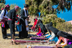 Priest blessing women weaving at Puno Peru. Puno, Peru - July 25, 2013: priest blessing women weaving in the peruvian Andes at Taquile Island on Puno Peru at Stock Images