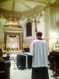 Priest carrying Cross before Mass