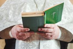 Priest in church reads. Prayer during religious rite. Book, ceremony stock photos