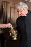 Priest collecting money. In church for fundraising Stock Image