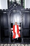 Priest in confession booth Stock Image